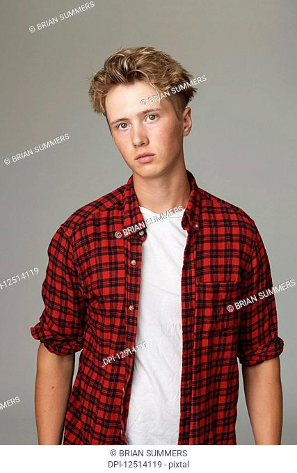 Portrait of a teenage boy wearing a red plaid shirt against a gray background