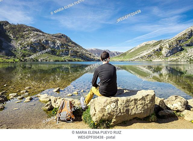 Spain, Asturias, Picos de Europa National Park, man sitting at Lakes of Covadonga