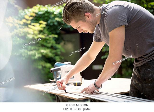 Construction worker measuring wood in driveway