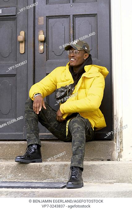 stylish man sitting on stairs in front of door, Munich, Germany