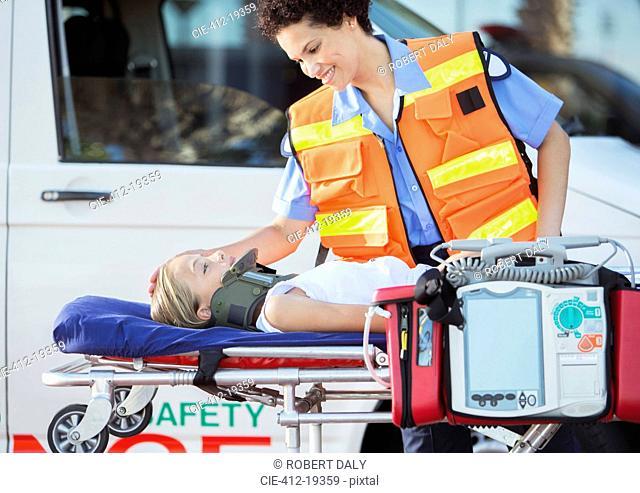 Paramedic examining patient on stretcher