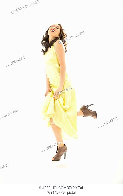 Beautiful young woman happy, celebrating in vintage yellow dress, full length in brown heels