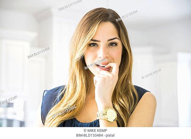 Mixed race woman biting her nail