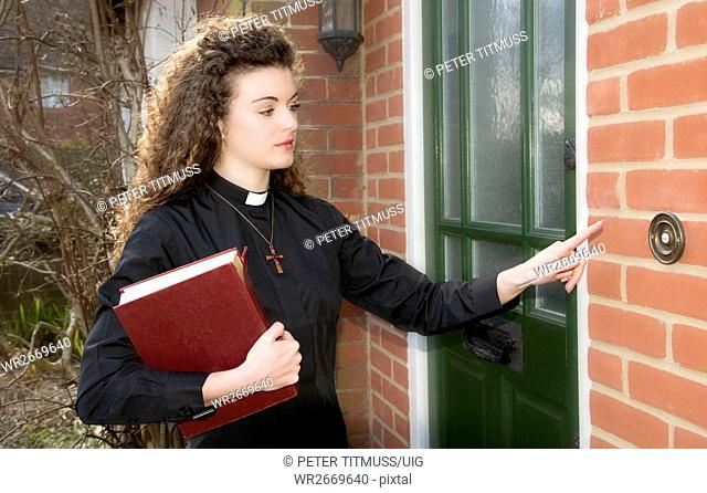 Young woman priest ringing door bell of a house