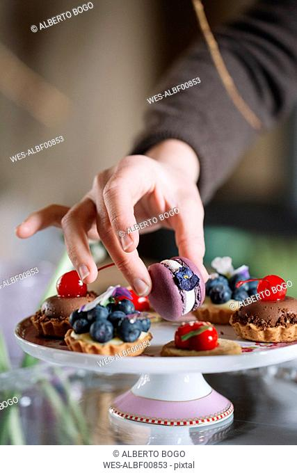 Woman's hand arranging Macaron on cake stand, close-up
