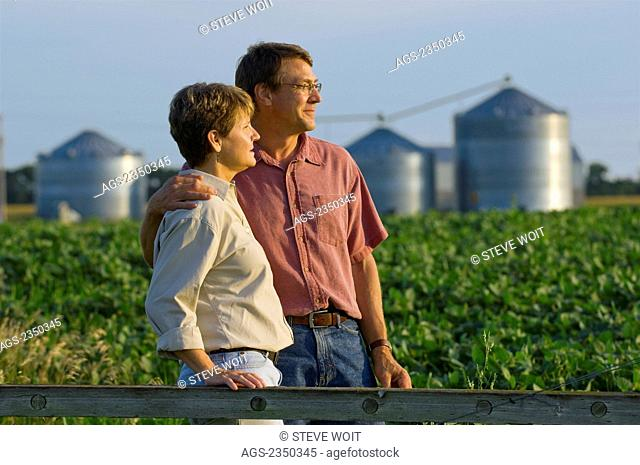 Agriculture - Husband and wife farmers in their mid growth soybean field share some personal moments together, with grain bins in the background / Minnesota