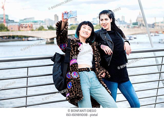 Two young stylish women taking smartphone selfie on millennium footbridge, London, UK