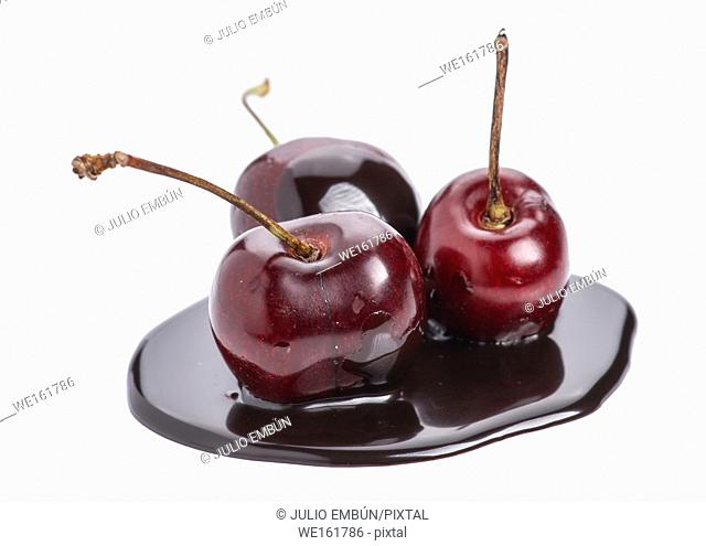 group of cherries in chocolate puddle isolated on white
