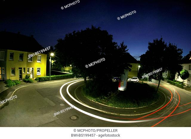 light streaks of cars in a roundabout of housing estate