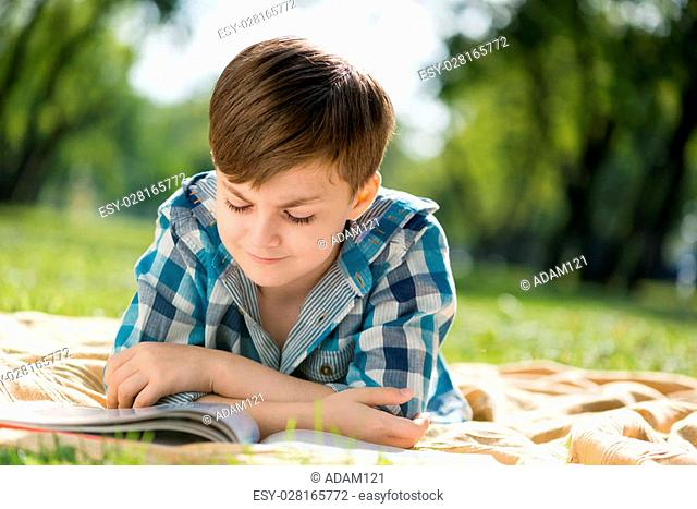 Cute boy in summer park lying on blanket and reading book