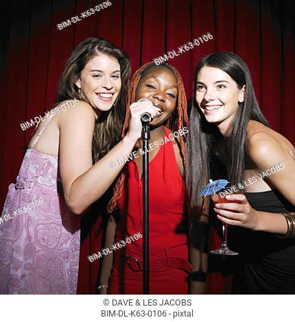 Three female friends with microphone, Perth, Australia