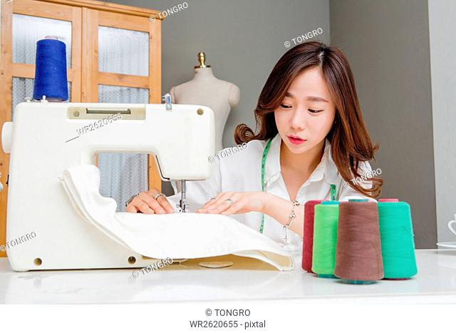 Portrait of female fashion designer sewing