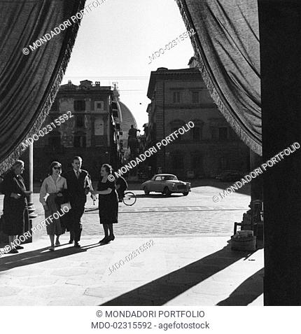 A woman trying to sell some candles to two people at the entrance of the Basilica della Santissima Annunziata. Florence, September 1955