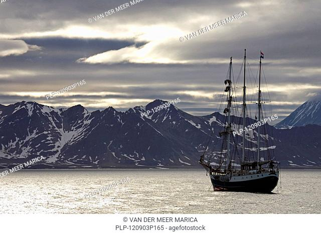 View over mountain range and the tall ship / barquentine Antigua at Svalbard, Spitsbergen, Norway