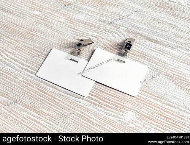 Blank plastic badges on light wood table background. Space for text. White id cards