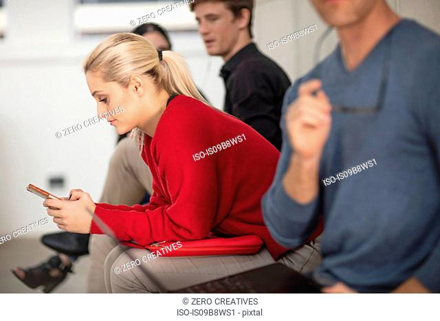 Male and female office workers looking using laptop and smartphone in meeting