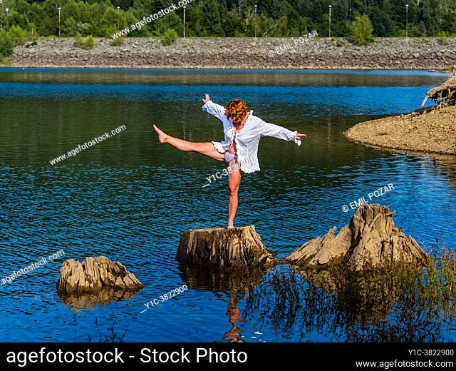 Balancing attractive adult woman performing on tree stump