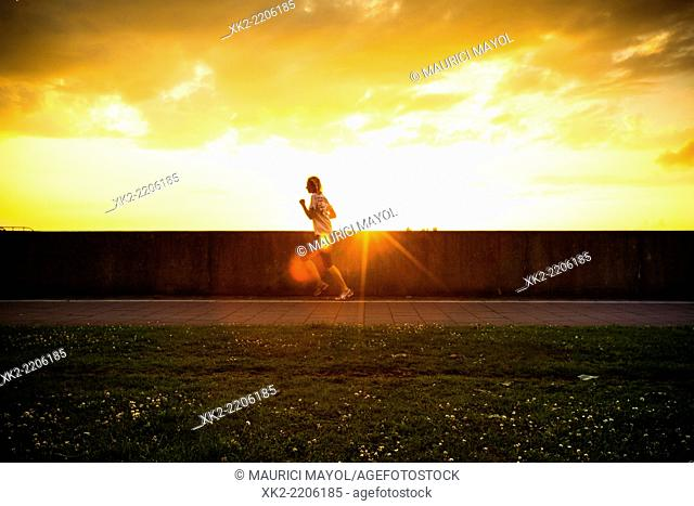 Healthy woman running at sunset