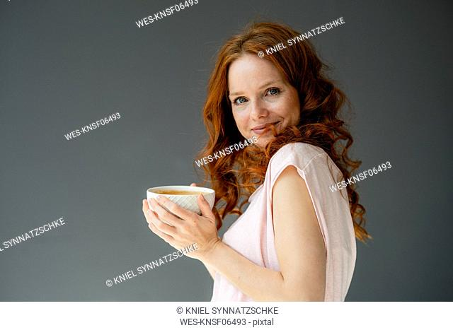 Portrait of smiling redheaded woman with coffee bowl against grey background