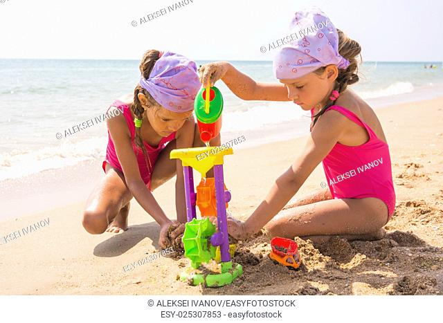 Two children playing with toys in the sand on the sea beach
