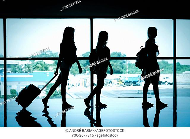 Silhouette of 3 female travelers at airport terminal