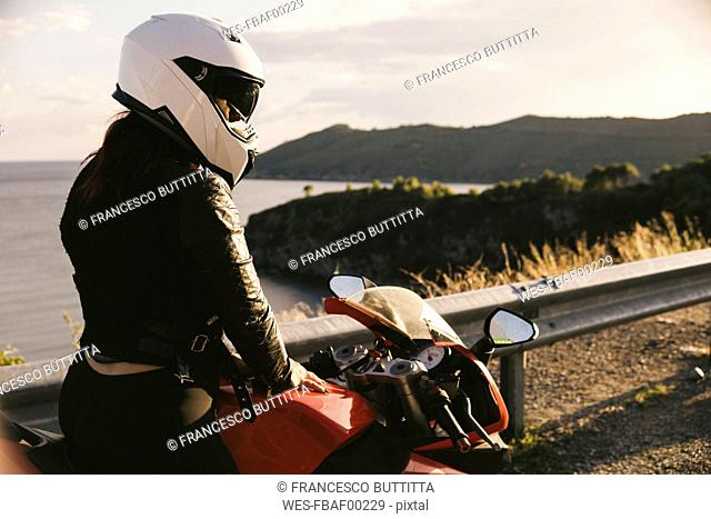 Italy, Elba Island, female motorcyclist at viewpoint