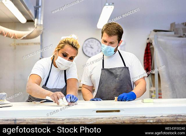 Man and woman polishing door while standing by workbench at workshop