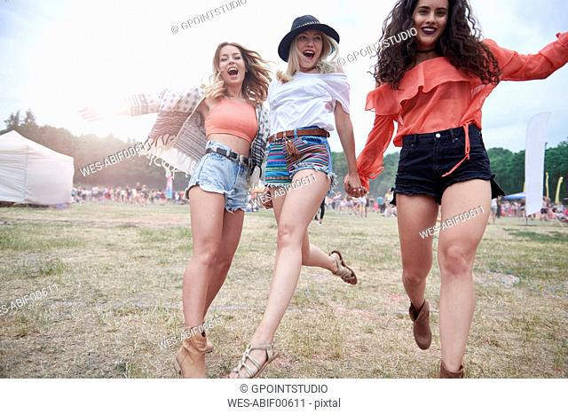 Cheerful friends holding hands and running at a music festival