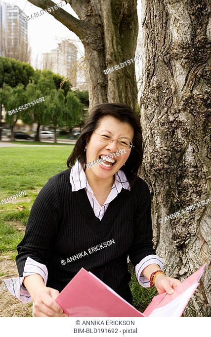 Chinese woman holding folder next to tree