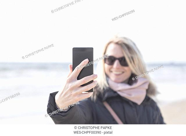 Woman taking selfie with cell phone on the beach
