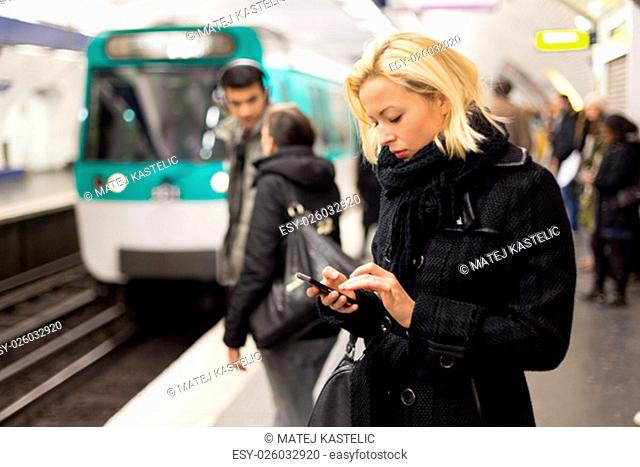 Young woman in winter coat with a cell phone in her hand waiting on the platform of a railway station for train to arrive. Public transport