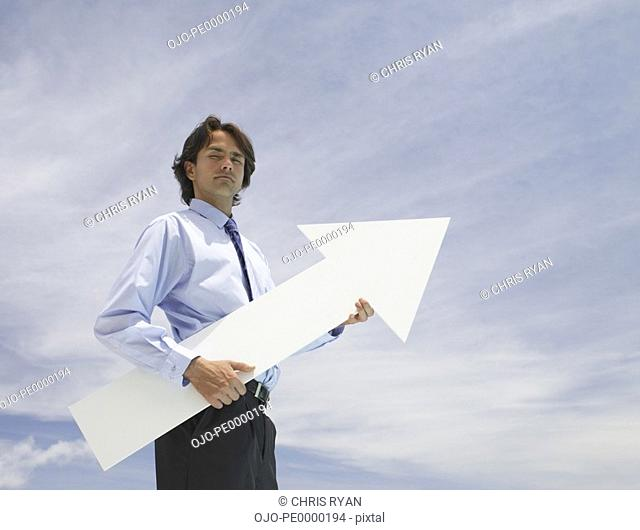 Businessman outdoors holding blank arrow with sky in background