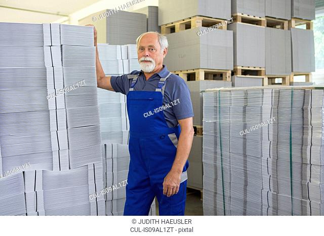 Factory worker moving and stacking cardboard
