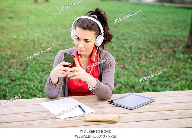 Young student with smartphone and digital tablet hearing music with headphones
