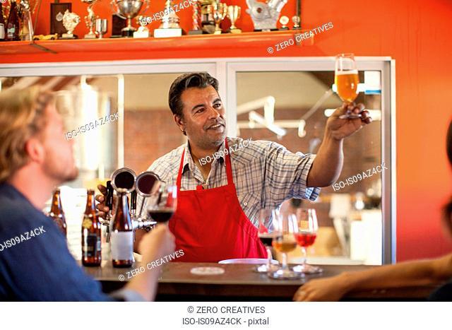 Bartender in public house holding beer glass smiling