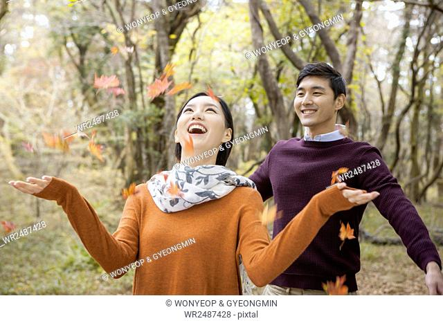 Portrait of young smiling couple throwing fallen leaves looking up in forest
