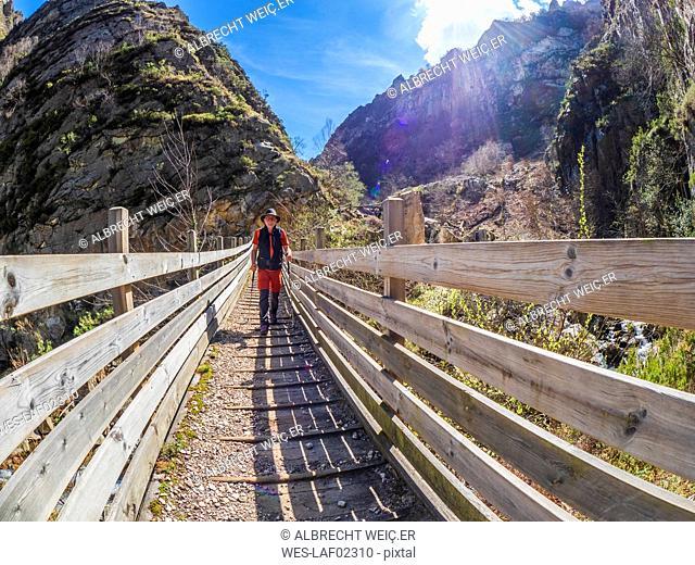 Spain, Asturia, Cantabrian Mountains, senior man on a hiking trip crossing a bridge