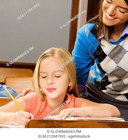Schoolgirl studying in a classroom with her teacher smiling behind her