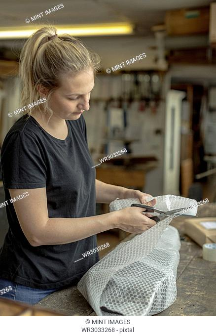 Blond woman standing in a workshop, cutting bubble wrap with pair of scissors, wrapping a parcel for delivery or posting