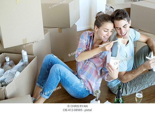 Couple sharing Chinese take out food in new house