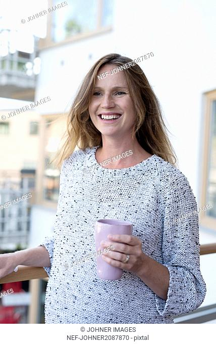 Smiling pregnant woman holding mug