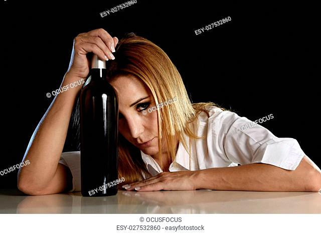 drunk blond woman alone in wasted depressed expression looking thoughtful and sad holding red wine bottle against her forehead isolated on black in alcohol...