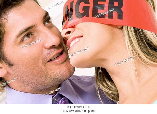 Close-up of a mid adult man with a blindfolded young woman