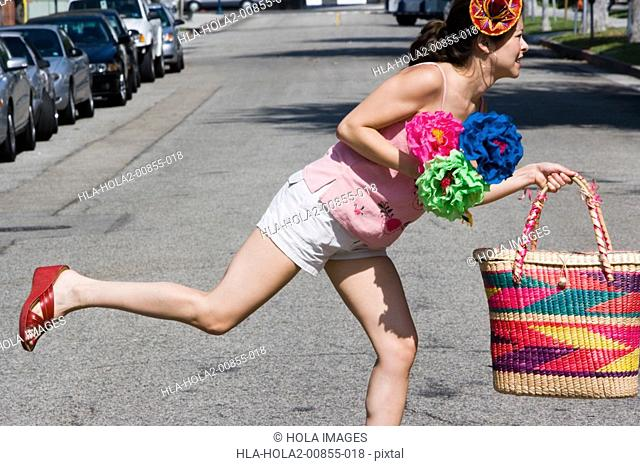 Woman crossing the street carrying bag and flowers