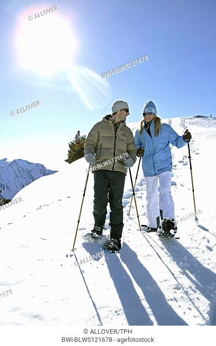 couple in winter, hiking with snow shoes