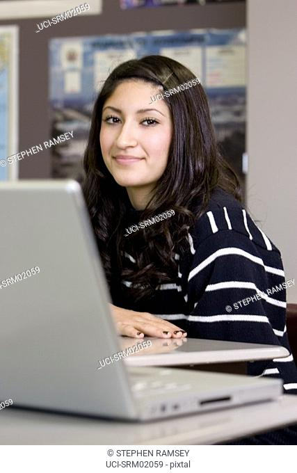 Teenage girl in classroom with laptop