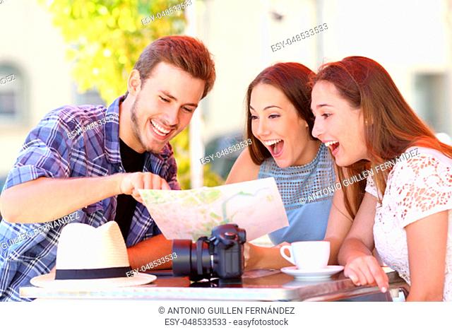 Three happy tourists checking paper guide sitting in a coffee shop