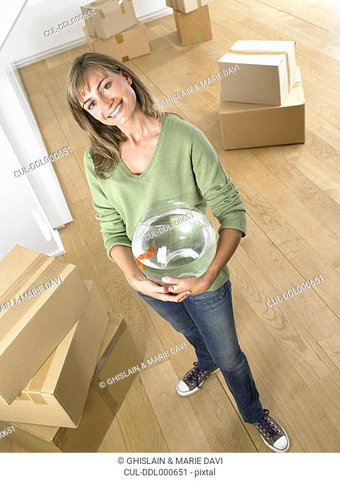 Woman holding fishbowl in new home smiling