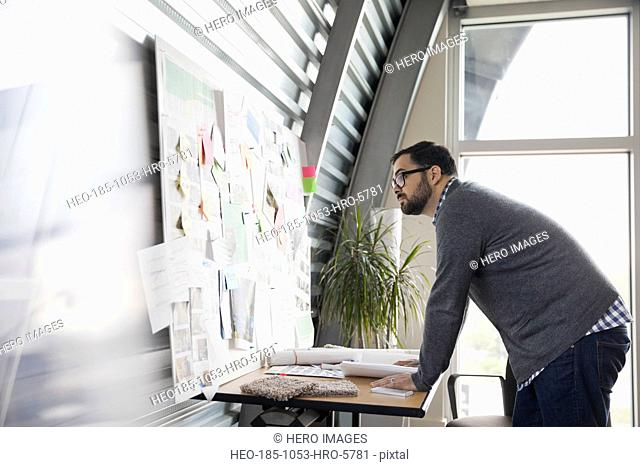 Businessman looking at bulletin board in office