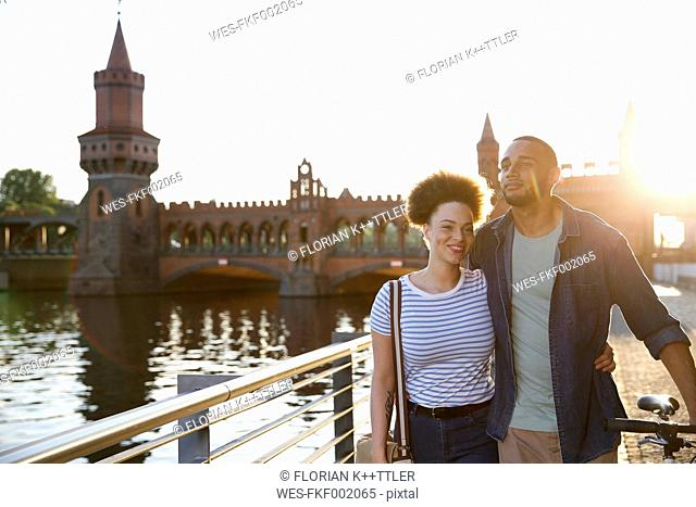 Happy young couple walking by river